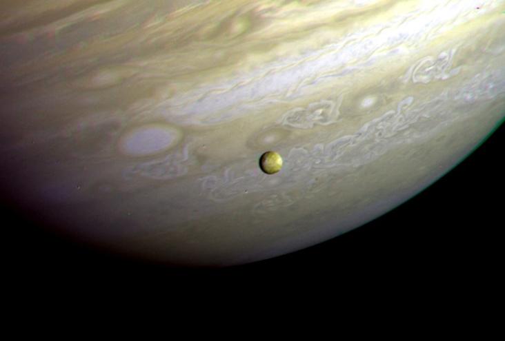 Ио на фоне турбулентных облаков Юпитера