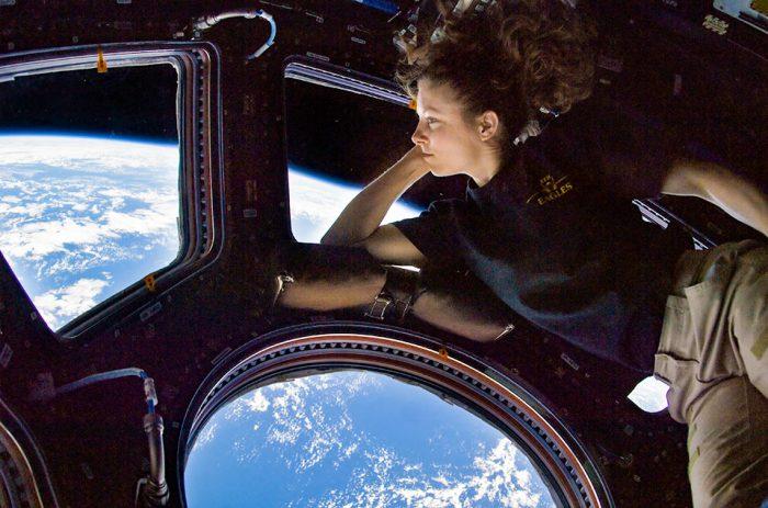 Астронавт НАСА Трейси Колдуэлл Дайсон, бортинженер экспедиции 24, смотрит в окно в куполе Международной космической станции. Сине-белая часть Земли и чернота космоса видны через окна.